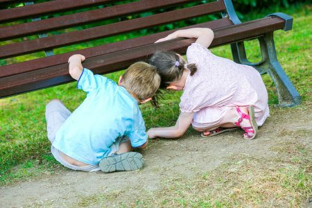 Two cute kids looking for something under the bench in the park