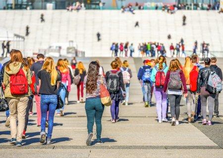 Photo pour Beaucoup de beaux jeunes colorés marchant vers les escaliers de la zone universitaire - image libre de droit