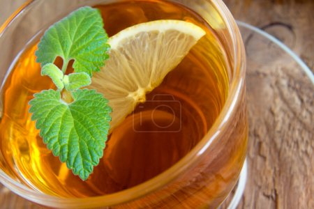 Tea with lemon and mint leaves in transparent cup ...