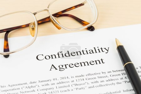 Confidentiality agreement document with glasses cl...