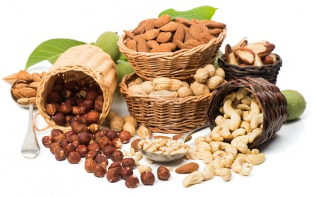 Photo for Variety  nuts  (shelled and in their shells)  including almonds, cashew, hazelnuts, brazil nuts, peanuts, green walnuts with leaves and pine nuts.  Isolated on white background - Royalty Free Image
