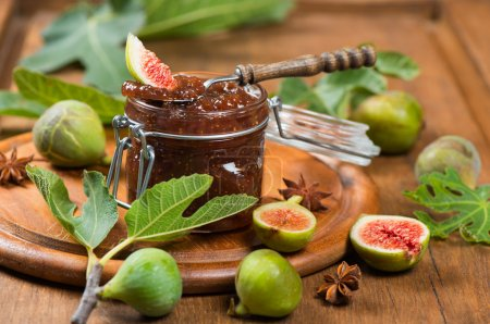 Fig  jam in glass with on spoon and fresh fruits w...