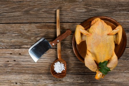 Uncooked  chicken on a old wooden table, top view
