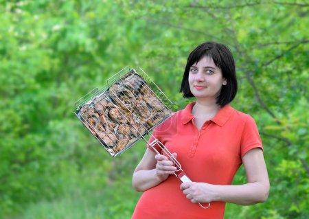 Photo pour Brochettes de morceaux de poisson. Belle femme brune dans les bois, nature est titulaire d'un treillis avec du poisson frit - image libre de droit