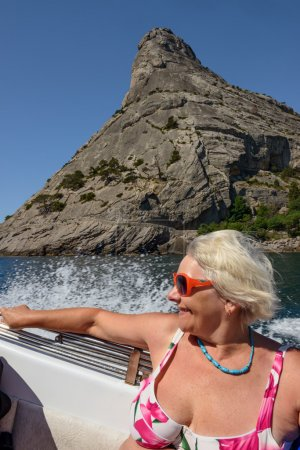 Senior lady is in sea boat on cliff background, Crimea.