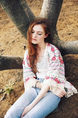 Outdoor fashion photo of young hippie caucasian model