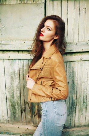 Photo pour Veste en cuir marron et jean taille haute. Belle femme d'automne avec des libs rouges et des cheveux bouclés. Style bohème artistique . - image libre de droit