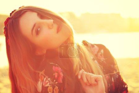 Fashion shot of a beautiful boho style girl over sunlight background.