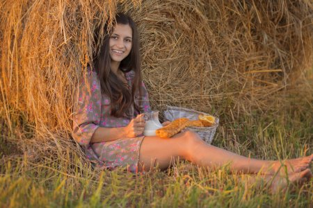 Smiling brunette with a jug of milk sits in a haystack