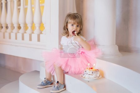 The girl on the stairs, trying cake birthday