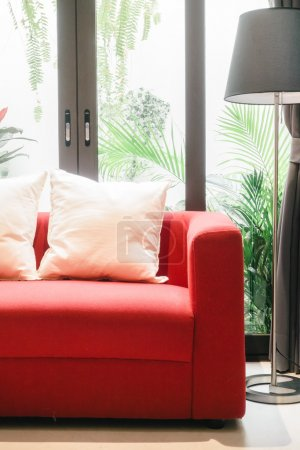 Red sofa with pillows and light lamp