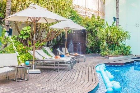 Photo pour Piscine parasol et chaise autour de la belle piscine de luxe dans la station hôtelière - Filtre Vintage Light film - image libre de droit