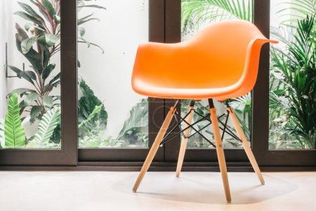 Photo pour Chaise orange avec décoration de lampe de lumière dans le salon intérieur - Vintage Light Filter - image libre de droit