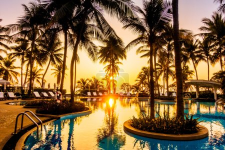 Photo for Beautiful luxury outdoor umbrellas and chairs around swimming pool with silhouettes of coconut palm trees in hotel resort, Vintage Filter - Royalty Free Image