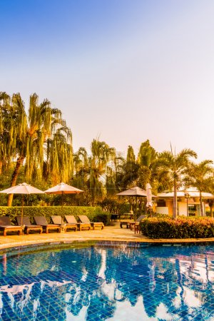 Photo for Beautiful luxury umbrellas and chairs around swimming pool in hotel resort at Sunset times, Vintage Filter and Boost up Color Processing - Royalty Free Image