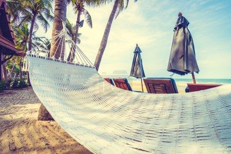 Photo pour Hamac vide sur la plage tropicale et la mer avec parasol et chaise - Filtre Vintage - image libre de droit