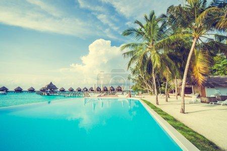 Photo pour Belle piscine extérieure de luxe avec parasol et chaise dans la station hôtelière aux Maldives - Boostez la couleur et l'effet de filtre Traitement - image libre de droit