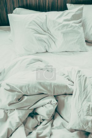 Photo for White sheet pillow on messy bed decoration in bedroom interior - Vintage Filter - Royalty Free Image