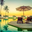 Sun loungers with umbrellas at pool with sunrise o...