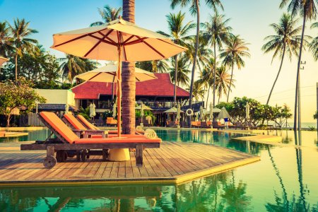 Sun loungers with umbrellas at pool