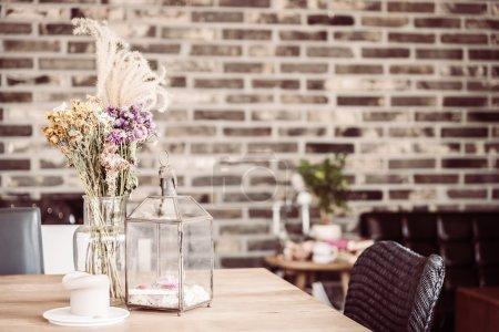 Photo pour Fleur sèche dans un vase et décoration de bougie dans un café-restaurant, effet filtre vintage - image libre de droit