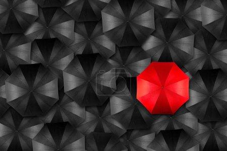 Photo pour Parapluie rouge au milieu des parapluies noirs - image libre de droit