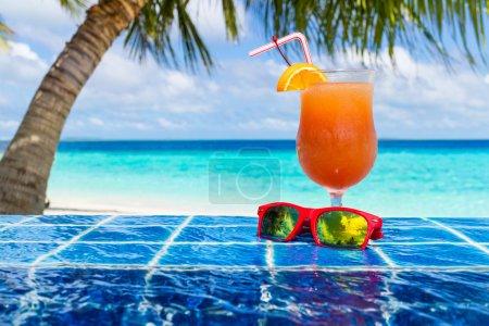 Photo pour Cocktail orange et des lunettes de soleil, au bord de la piscine à débordement - image libre de droit