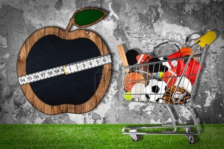 Photo pour Chariot rempli d'équipement sportif devant un mur de pierre avec tableau noir en forme de pomme - image libre de droit