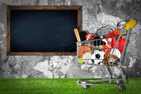 Photo pour Chariot rempli d'équipements sportifs devant un mur de pierre avec tableau noir - image libre de droit