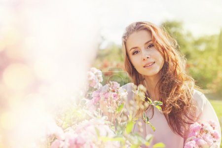 Photo for Portrait of young woman in a rose garden - Royalty Free Image