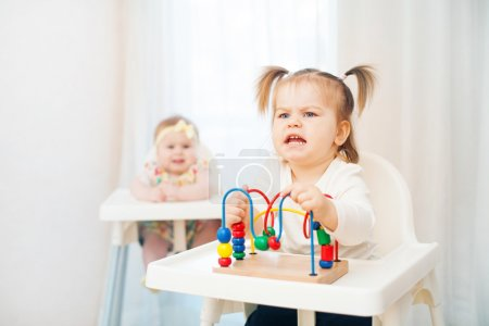 Photo for Two little girls in highchairs at home,one child  demanding - Royalty Free Image