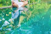 Woman meditating at pool side.