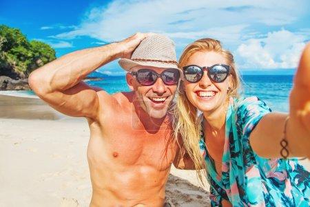 Foto de Feliz pareja tomando selfie en una playa - Imagen libre de derechos