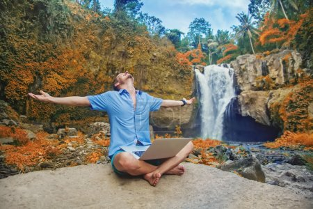 Photo for Successful man with laptop outdoors in a jungle - Royalty Free Image