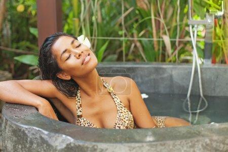 Woman having bath in a luxury spa salon