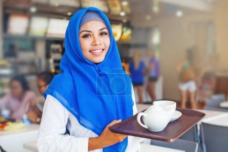 Photo pour Asiatique musulmane serveuse tenant un plateau avec du thé. Femme portant hijab travaillant dans un café - image libre de droit