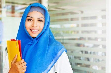 Photo pour Musulmane asiatique fille, collège étudiant, tenant ses classeurs dans une salle de classe - image libre de droit