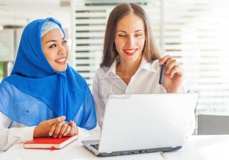 Photo pour Femme européenne et femme musulmane asiatique travaillant ensemble - image libre de droit