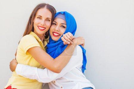 Photo pour Amitié de la notion de religions : musulmane et chrétienne fille ensemble - image libre de droit