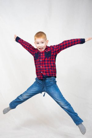 Photo pour A boy in a red plaid shirt and blue jeans jumped high, arms and legs outstretched. he has a big happy smile on his face - image libre de droit
