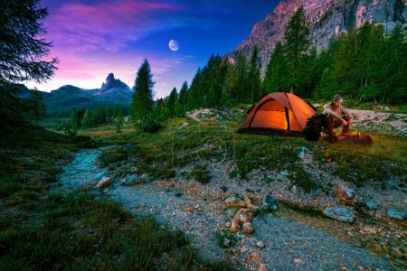 Hiker, campfire and tent