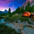 Mystical night landscape, in the foreground hiker, campfire and tent
