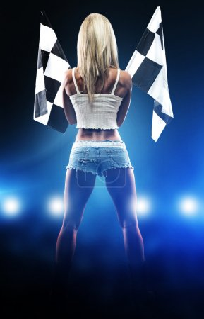 Photo pour Sexy blonde woman starts racing, holding flags in hands - image libre de droit