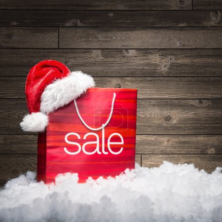 Photo for Christmas - Sale bag with Santa hat, rebate, on wooden background - Royalty Free Image