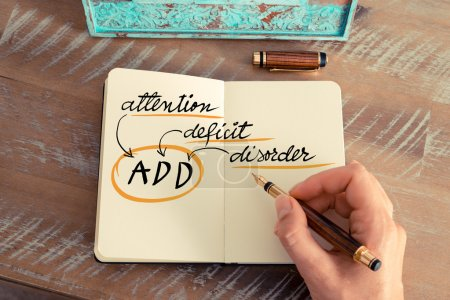 Photo for Retro effect and toned image of a woman hand writing a note with a fountain pen on a notebook. Acronym ADD Attention Deficit Disorder next to yellow lighting bulb - Royalty Free Image