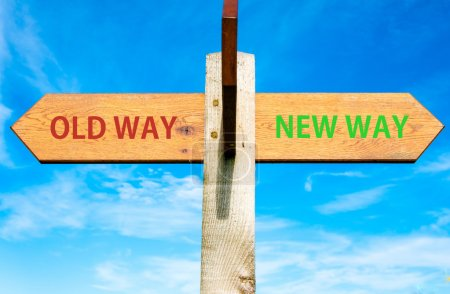 Wooden signpost with two opposite arrows over clear blue sky, Old Way and New Way signs, Life change conceptual image