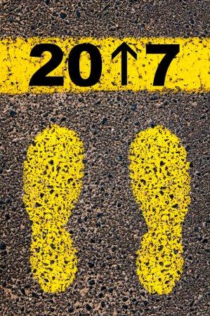 Photo pour L'année 2017 arrive, le numéro 1 est remplacé par une flèche pointant vers l'avant. Image conceptuelle avec des traces de peinture jaune sur la route en face de la ligne horizontale sur fond de pierre d'asphalte . - image libre de droit