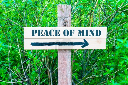 Photo pour PEACE OF MIND  written on Directional wooden sign with arrow pointing to the right against green leaves background. Concept image with available copy space - image libre de droit