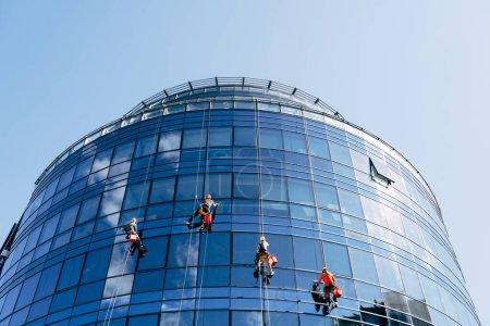 Photo pour Nettoyants pour vitres lavent les vitres bleues en miroir à l'extérieur du bâtiment. Photo de haute qualité - image libre de droit