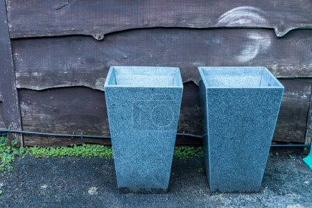 a close up view of two granite plant pots sitting new to a wooden fence